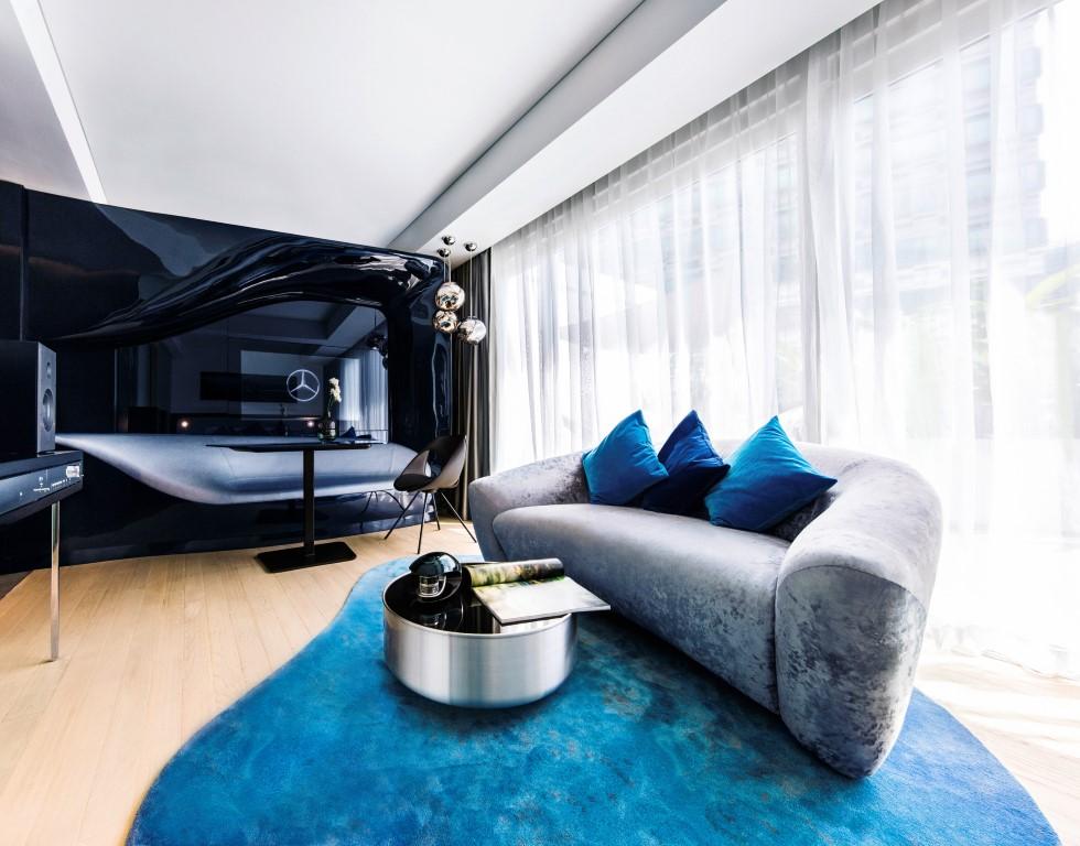 """Im Innern der großzügig dimensionierten Appartements wird der Blick sofort auf die """"Black Magic Wall"""" gezogen – eine vollständig in das Raumdesign integrierte Medienwand. Die schwarze Oberfläche versinnbildlicht einen einzigartigen Hightech-Look, der dem Lifestyle einer technophilen Generation entspricht. Weitere Highlights sind das silbergraue Sofa im Wohnraum und das Bett mit Kopfteil im Schlafbereich. Der Sessel ist ebenso wie die Sitzmöglichkeiten mit silberfarbenem Leder der S-Klasse bezogen. Für die Beleuchtung sorgt ein Kronleuchter mit Swarovski-Kristallen, die auch in den Scheinwerfern des Mercedes-Benz S-Klasse Coupés zu finden sind. Das Burmester® Soundsystem ist ein weiteres Highlight. Es vereint signifikante Designmerkmale mit einem exquisiten Hörvergnügen. Bemerkenswert ist auch eine Table-top-Version des Beduftungssystems, das mit dem Mercedes-Benz AIR-BALANCE Paket angeboten wird. Das System verstärkt die Wohlfühlatmosphäre des Raums mit dezenten Düften aus dem Angebot der S‑Klasse. Weitere Merkmale aus der Welt von Mercedes-Benz sind ein Fahrsimulator im Spin & Play Raum sowie Trekking-Fahrräder, mit denen Gäste die Stadt erkunden können. Die Appartements in Singapur können ab 15. April 2016 unter http://www.capribyfraser.com/en zu buchen. Die Preise beginnen bei 400 Singapur-Dollar (SGD) (rund 260 Euro) pro Tag."""